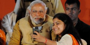 Chief Minister of the Indian state of Gujarat and Bharatiya Janata Party (BJP) prime ministerial candidate Narendra Modi (L) poses for a photograph as party candidate from Mumbai Poonam Mahajan takes a 'selfie' with him at an election rally in Mumbai on April 21, 2014. India's 814-million-strong electorate is voting in the world's biggest election which is set to sweep the Hindu nationalist opposition to power at a time of low growth, anger about corruption and warnings about religious unrest. AFP PHOTO/INDRANIL MUKHERJEE (Photo credit should read INDRANIL MUKHERJEE/AFP/Getty Images)