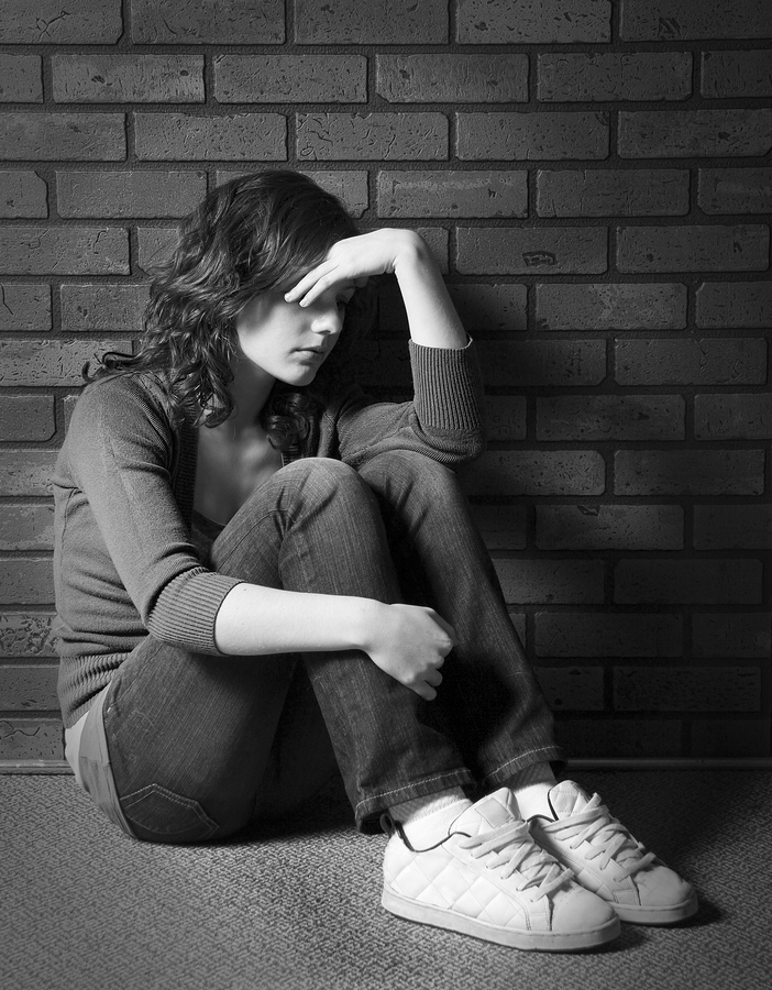 Teenage girl sitting against brick wall in depressed state